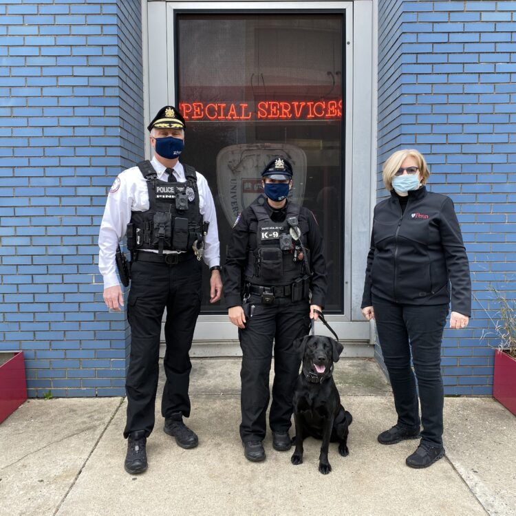 Deputy Chief Fink, Officer Wesley, K9 Officer Uman, and VP Rush pose in front of HQ