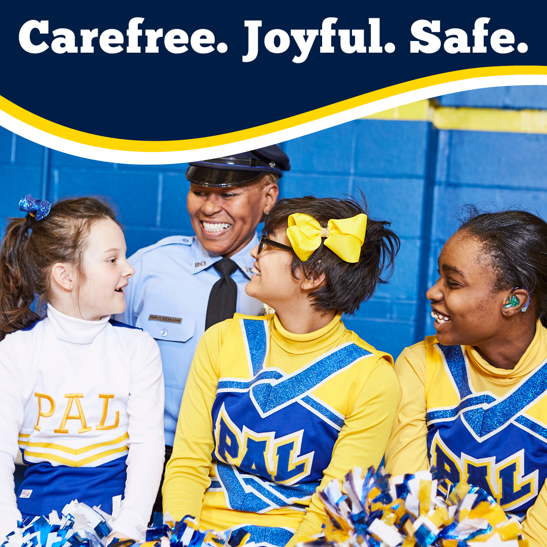 """Police Officer Cassandra Parks-DeVaughn smiling with three PAL Cheer team participants. """"Carefree. Joyful. Safe."""""""