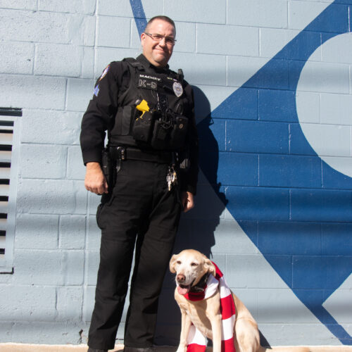 Sgt. Mackey with K9 Officer Zzisa. Zzisa is wearing a striped scarf in support of the Philadelphia Ronald McDonald House.