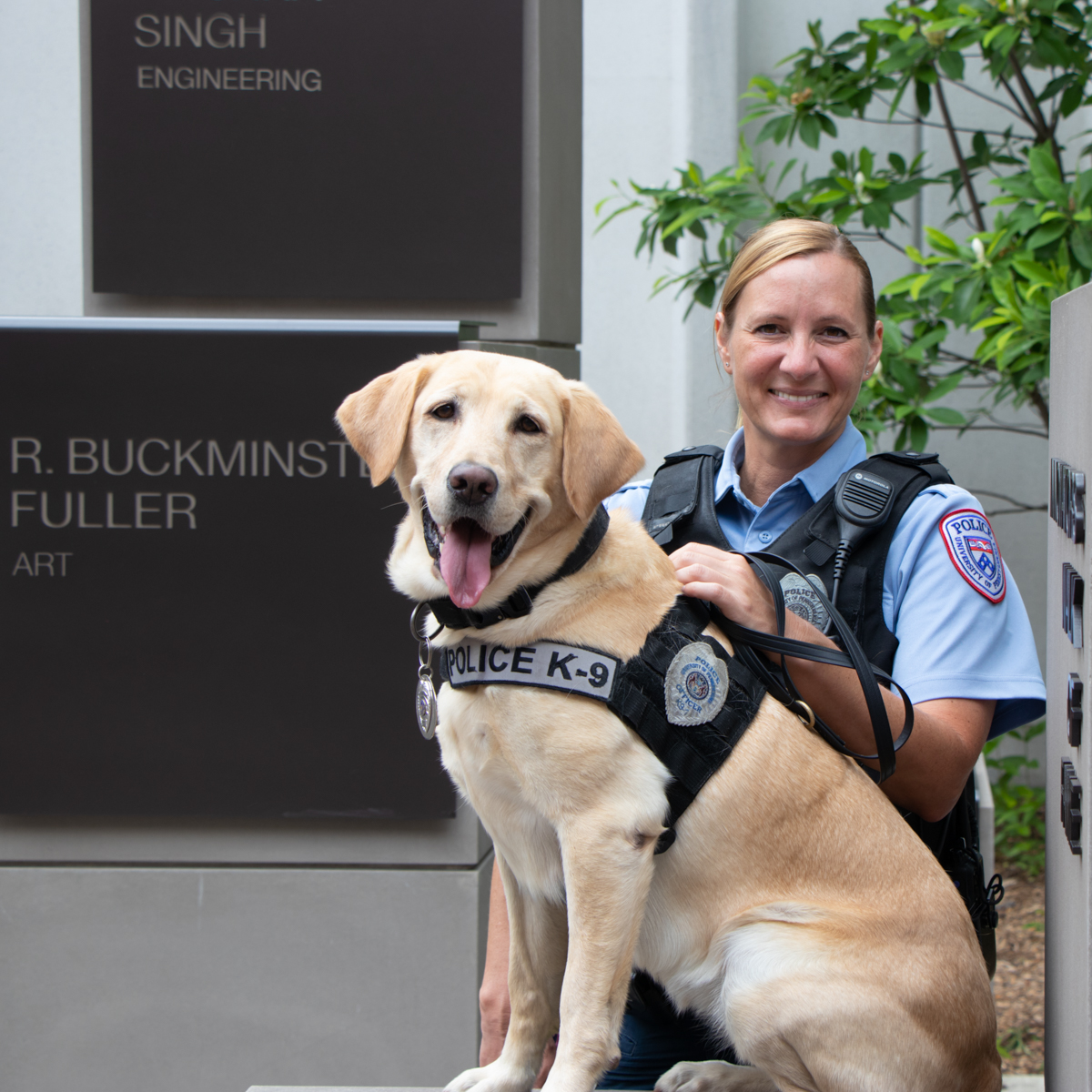 Officer Wesley poses outdoors with K9 Officer Socks, a yellow Labrador Retriever