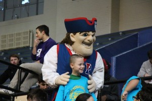 PAL student poses with the Penn Quaker, Penn's Athletic Department Mascot