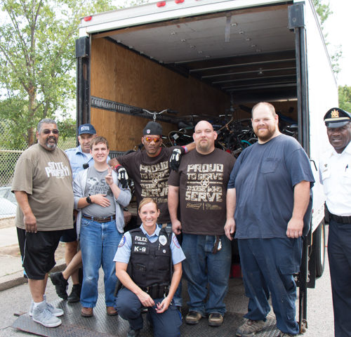 Staff from The Bike Shop load the donations with member of Penn Police